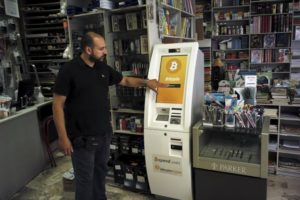 A man demonstrates the use of a Bitcoin ATM at a bookstore in Acharnai in northern Athens, Greece June 30, 2015. REUTERS/Dimitris Michalakis
